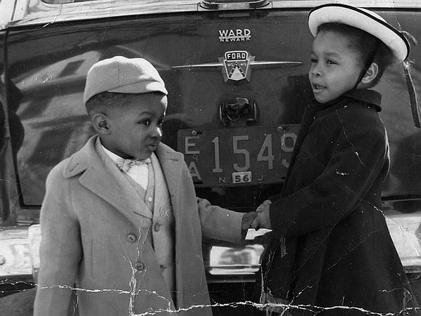 Two young children by car. Gretchen Sorin personal collec...