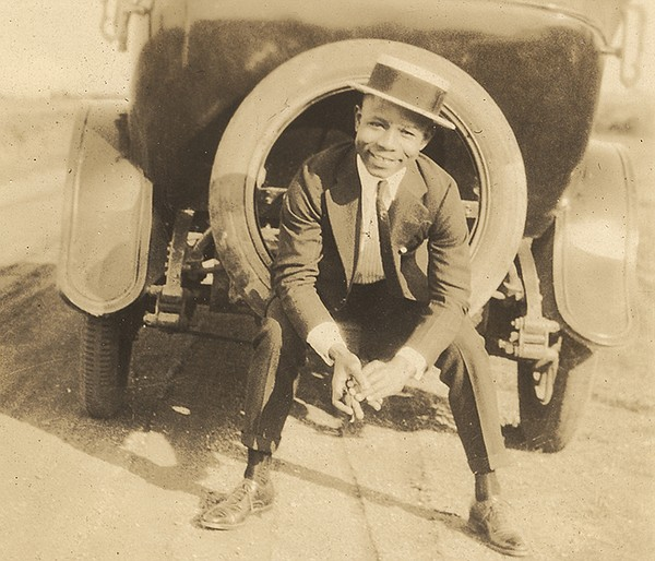 Young African American man sitting in the spare tire on t...