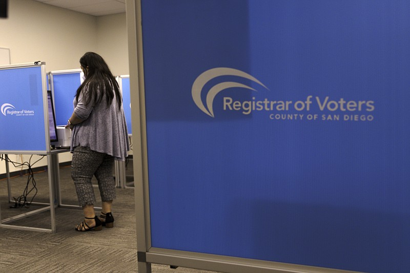 A woman is shown voting at the Registrar of Voters in Kearny Mesa in this Oct...