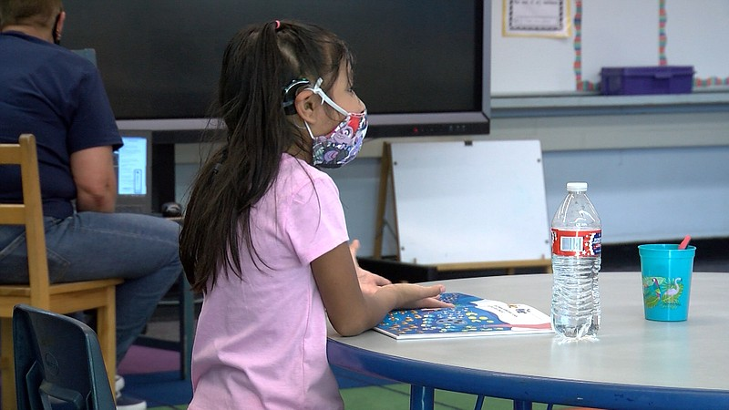 A young girl with a face mask sits at a desk at Lafayette Elementary School i...