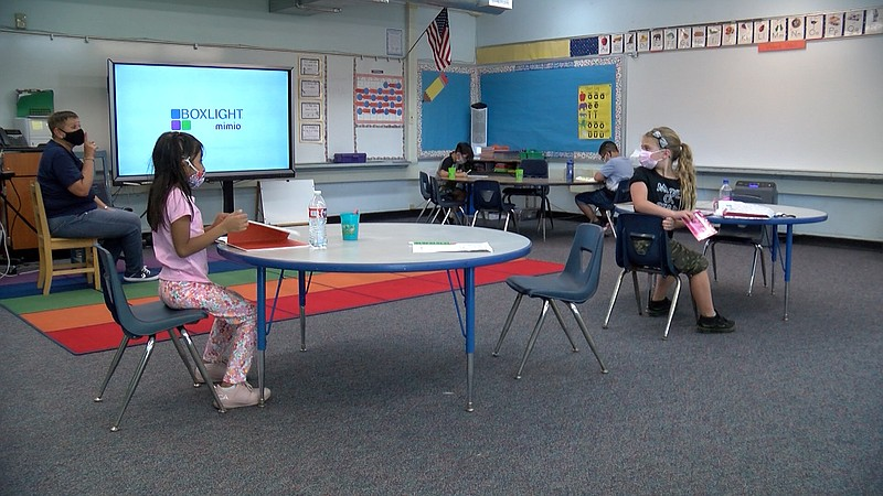 Four students sitting at desks 6 feet apart as a teacher guides them through ...