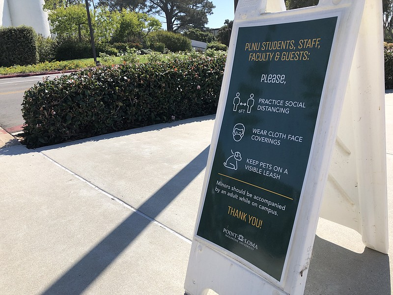 A sign reminding people of COVID safety measures is shown on the campus of Po...