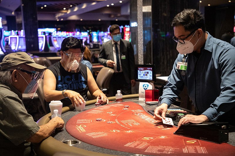 Two visitors wear face shields and masks while at a card table at the Sycuan ...