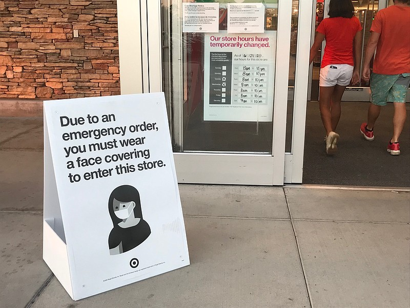 A sign indicating the store's coronavirus prevention policies sits outside th...