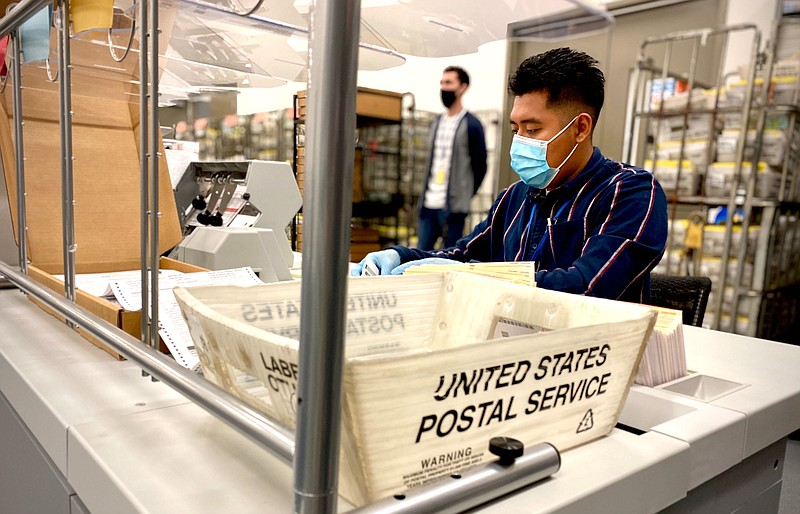 A worker with a face mask and gloves sorts through mail-in ballots at the San...