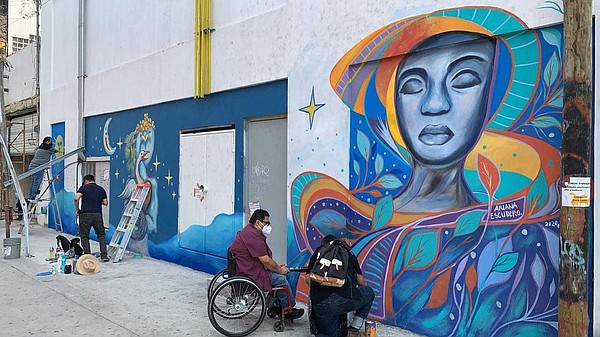 Artists work on Ariana Escudero's mural in Tijuana on Sep...