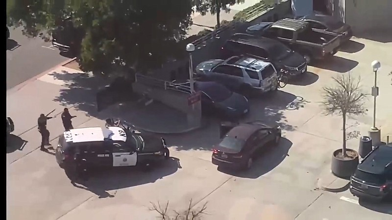Police officers in a standoff against an armed, agitated woman who drove into...