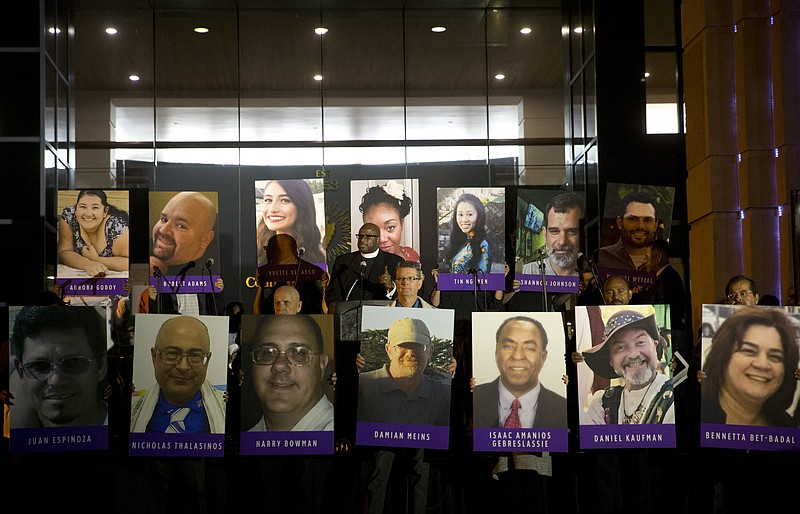 In this Dec. 7, 2015, file photo, San Bernardino County employees hold up pho...