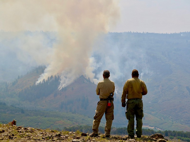 Firefighters watch a controlled burn within the Grizzly Creek Fire in Colorad...