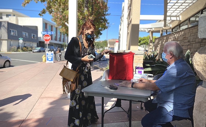 A San Diego resident drops off her ballot at a ballot drop off location at th...