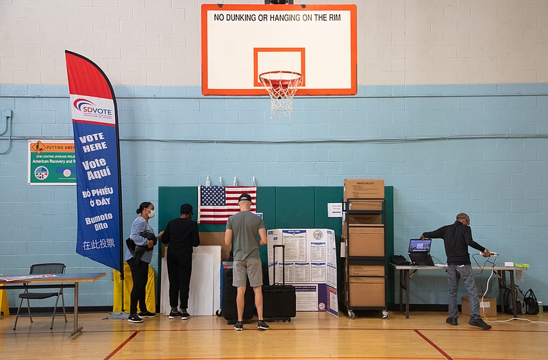 Poll workers set up for the start of in-person voting at the Mid-City Gym in ...