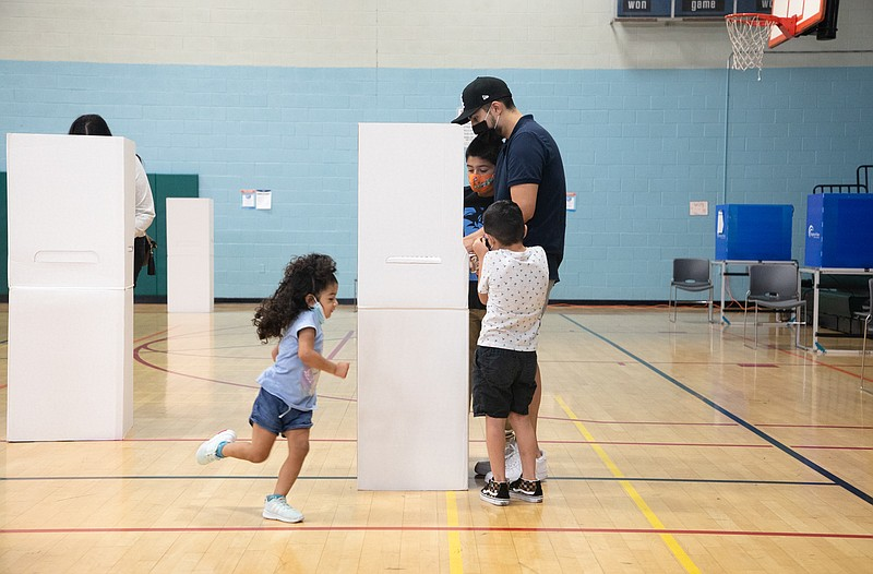 Hector and Maribel Hernandez fill out ballots with their three children at th...