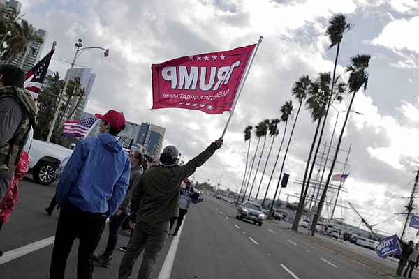 San Diego residents fly flags and hold signs in support o...