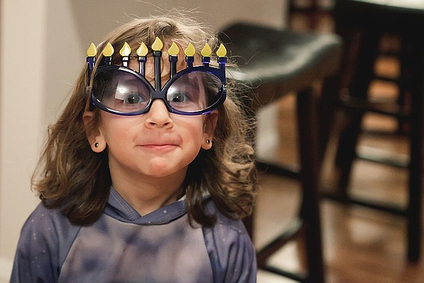 A young girl wears special Hanukkah glasses.