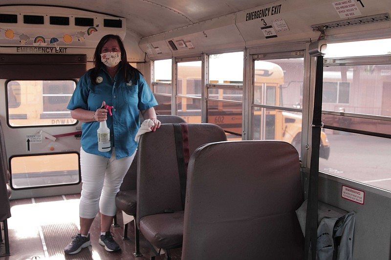 Kim Denson, a bus driver at Poway Unified School District, disinfects her sch...