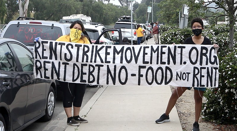 Protesters hold up a sign as part of a rent strike caravan that drove through...