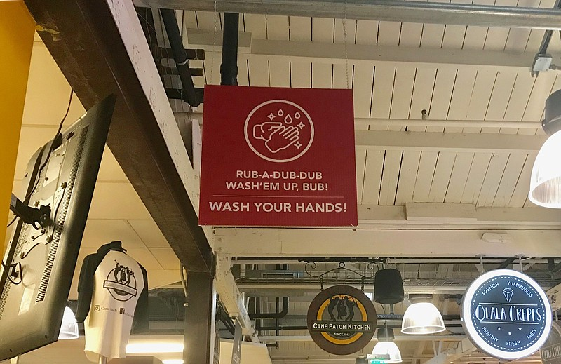 A sign hanging from the ceiling reads
