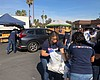 Volunteers help to load cars of military famili...