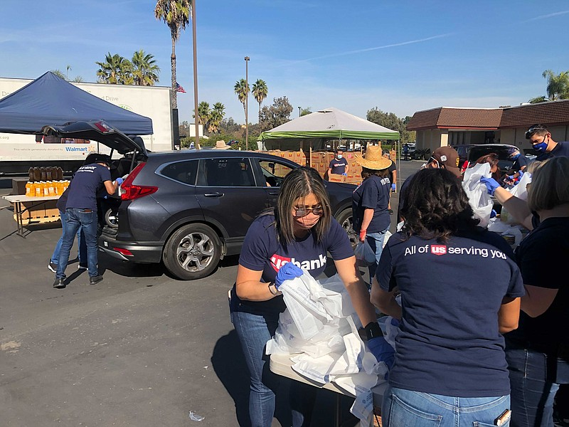 Volunteers help to load cars of military families with food and essential goo...