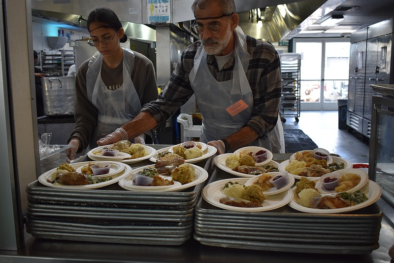 Father Joe's Villages volunteers plate Thanksgiving meals for homeless San Di...
