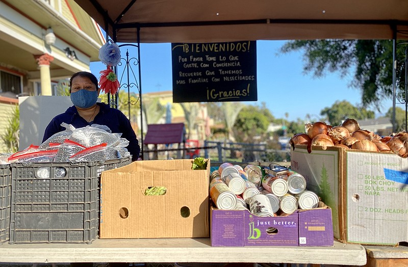 Araceli Mauricio volunteers at a pop-up food donation stall in Sherman Height...