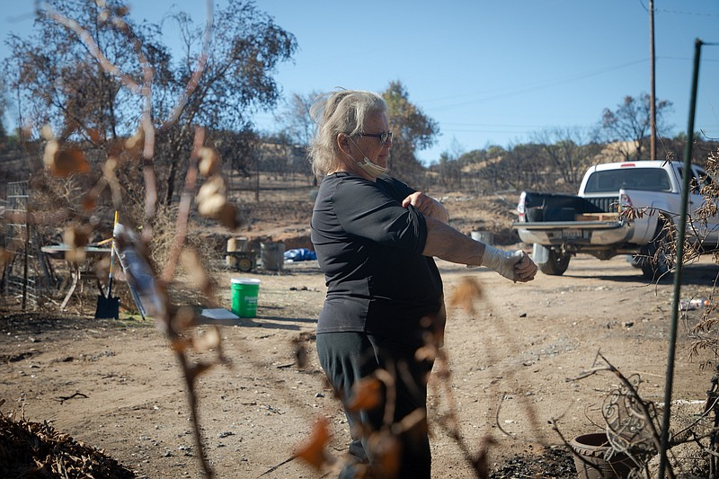 Eileen Menzies works to clear her property in Lawson Valley, which burned dur...