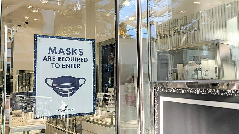 A sign at the Swarovski store in Fashion Valley Mall asking shoppers to don a...
