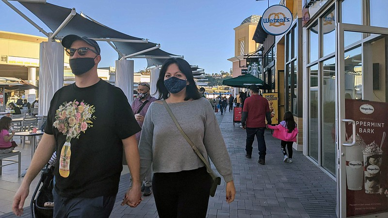 Shoppers wearing masks at the Fashion Valley Mall food court in this file pho...