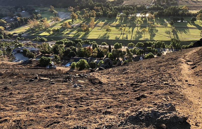 A burned hillside is pictured after a brush fire in Rancho San Diego destroye...