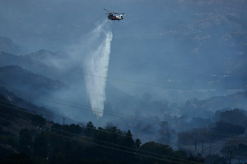A helicopter drops water as the Bond Fire burns in Silverado, Calif., on Thur...