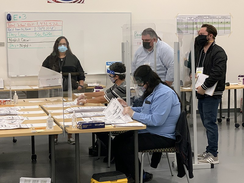Observers look over the shoulders of election workers recounting ballots in t...