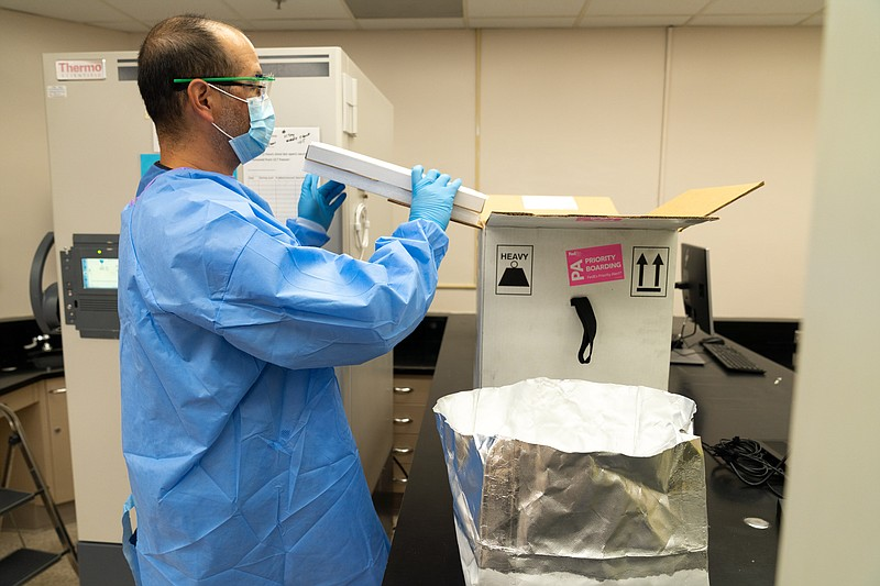 The UC San Diego Health Pharmacy team unpacks the first shipment of the Pfize...