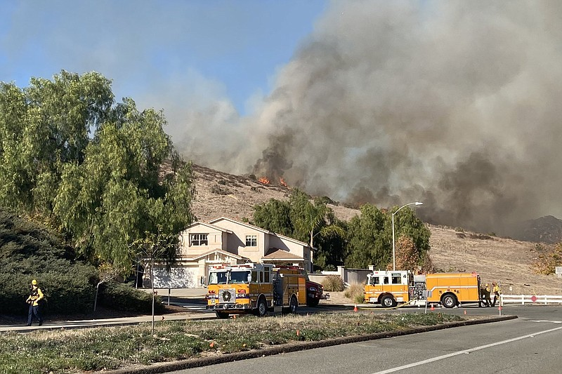 Flames are seen on the hillside in Santee at the Chaparral Fire on Dec. 16, 2...