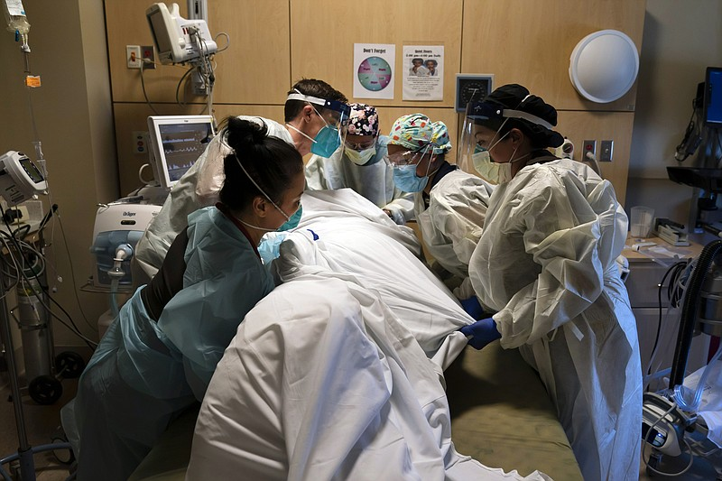 In this Nov. 19, 2020, file photo, medical personnel prone a COVID-19 patient...