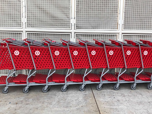 A line of grocery carts are shown parked in front of a Sa...
