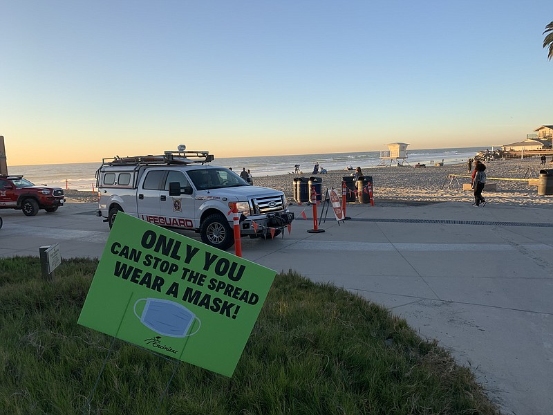 A sign in the sand reminds beachgoers to wear a mask at Moonlight State Beach...