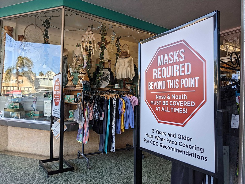 A sign in front of a store in Encinitas advising customers that masks are req...
