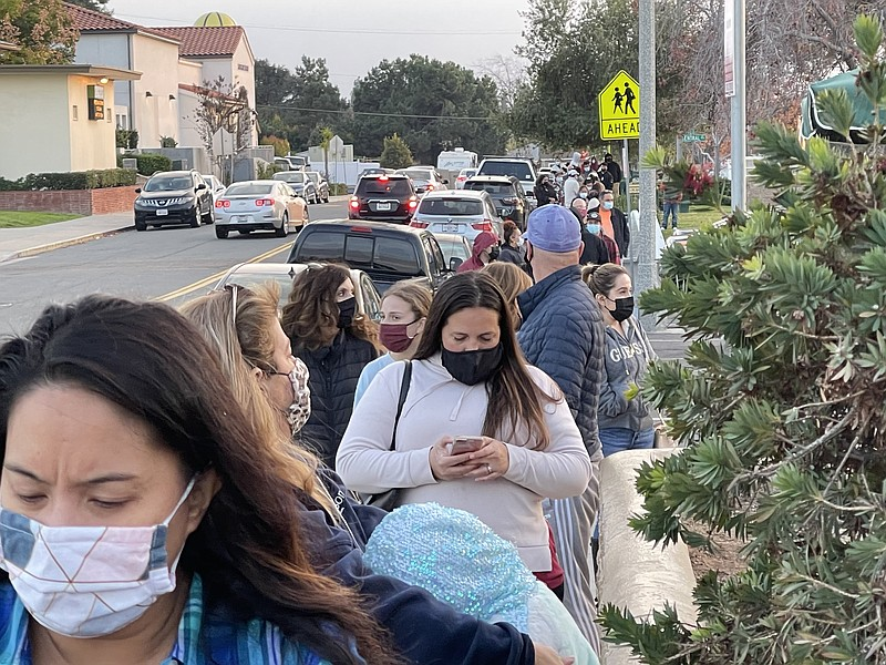People wait in line to get tested for COVID-19 at the Lemon Grove Community C...