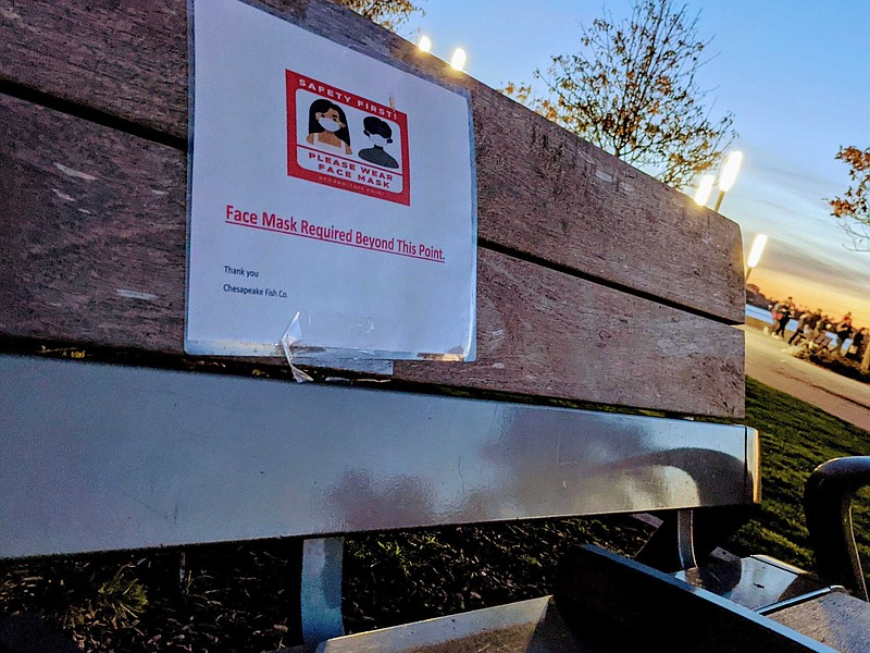 A sign on a bench at Seaport Village advising people to wear a mask, Jan. 2, ...