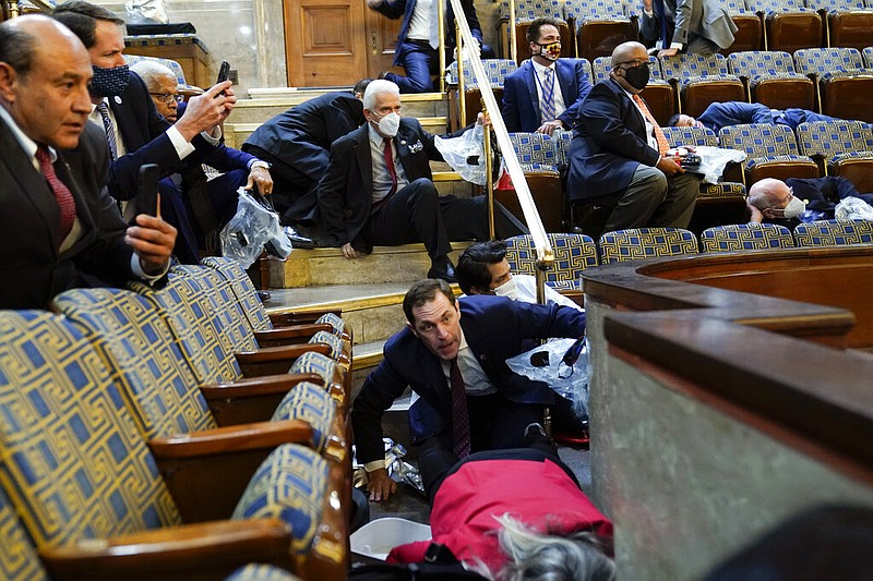 People shelter in the House gallery as protesters try to break into the House...