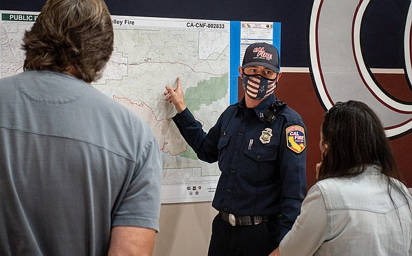 A firefighter shows a map of the Valley Fire to people at...