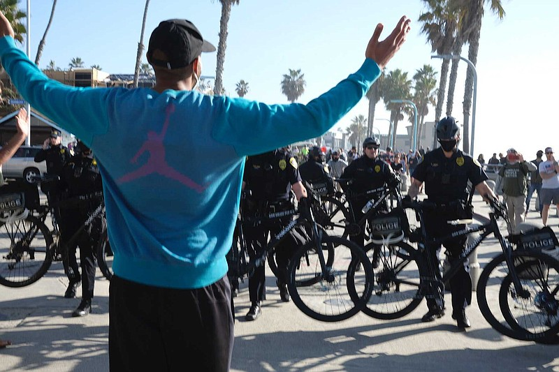 A protester raises his arms towards police officers at a demonstration betwee...
