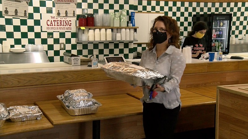 Encinitas resident Syndee Wood carrying a tray of burritos from Chicks Natura...