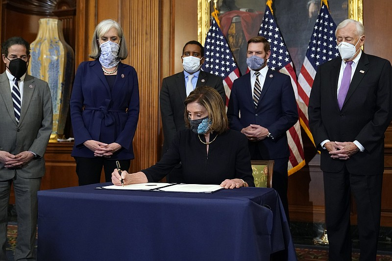 House Speaker Nancy Pelosi of Calif., signs the article of impeachment agains...