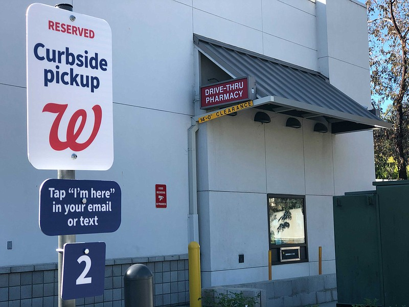 A Walgreens curbside pickup sign stands adjacent to the company's drive-thru ...