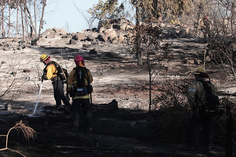 Firefighters putting out hot spots in the Comet Fire in San Marcos on Jan. 14...