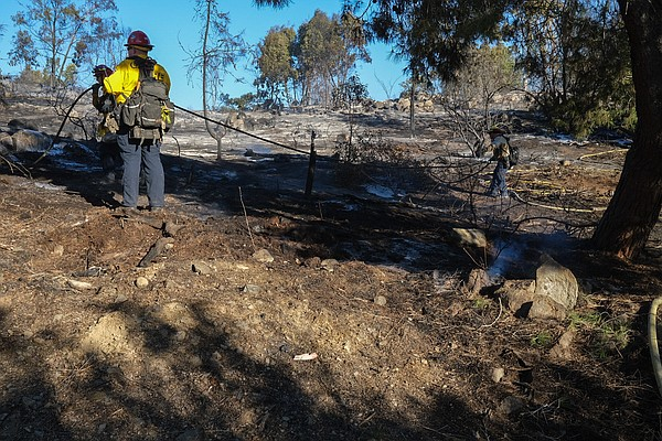 Firefighters putting out hot spots in the Comet Fire in S...