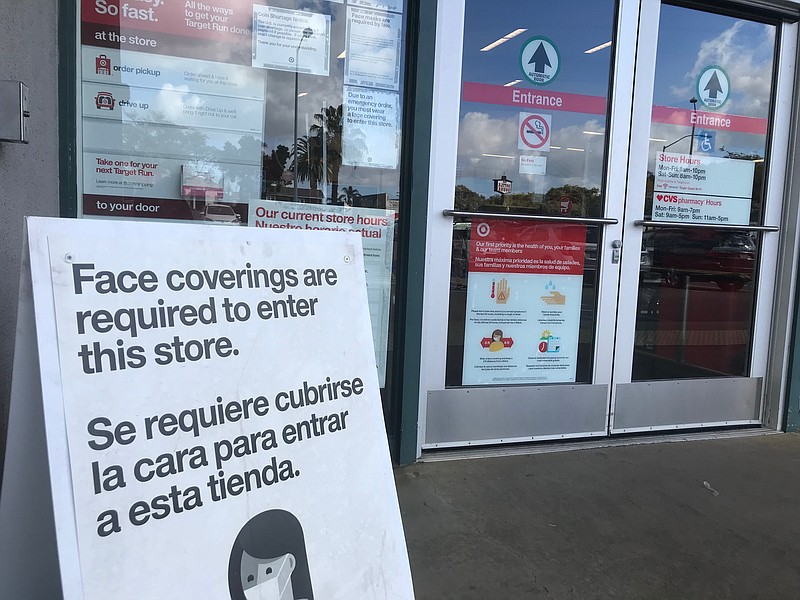 A sign advising of the store's COVID-19 prevention policies sits outside Targ...
