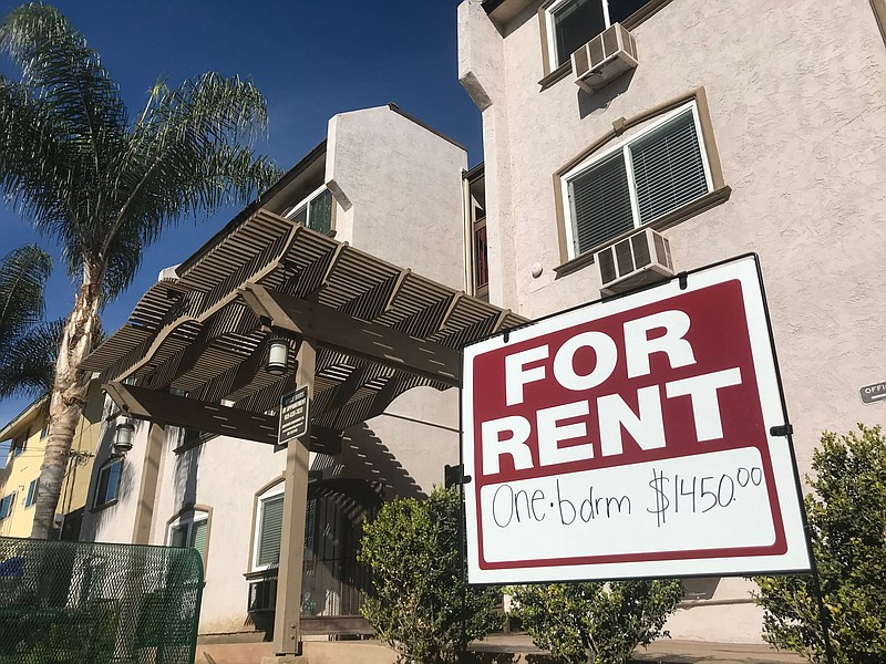 A sign advertises a one bedroom apartment for rent in front of a building in ...