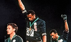 Tommie Smith and John Carlos, hold their fists ...